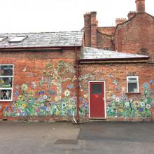 brick wall covered in mosaic flowers, birds, butterflies and bugs.  school project